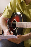 Songwriting on acoustic guitar. Songwriting on a red sunburst acoustic guitar royalty free stock photos