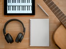 Song Writing. Songwriting Tools, Headphone, Guitar, Notebook, Electronic Tablet and Pen on Wooden Background Top View Royalty Free Stock Photos