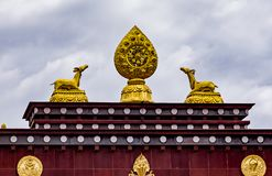 Songzanlin Tibetan Buddhist Monastery, Zhongdian, Yunnan - China. Rooftop statues of two golden deer and Dharma wheel in Songzanlin Tibetan Buddhist Monastery Stock Image