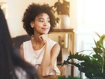 Sonhando a menina afro-americano que senta-se no caf? e em admirar o por do sol fotografia de stock