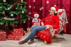 Sonhando a mulher do Natal na cadeira imagens de stock