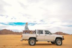 Sonhando a mulher que senta-se em um jipe no tempo da excursão no deserto de Wadi Rum Fotografia do conceito do curso fotos de stock royalty free
