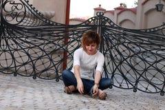 Sonhando a mulher que senta-se para baixo fora Fotos de Stock