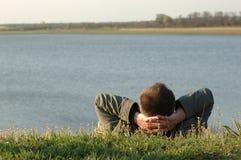 Sonhando o homem no banco de rio Fotografia de Stock Royalty Free