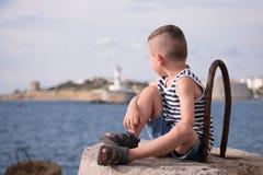 Sonhando o rapaz pequeno que olha na distância na perspectiva de um mar ajardine Fotos de Stock