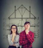 Sonhando os pares que planeiam o esboço da casa nova foto de stock royalty free