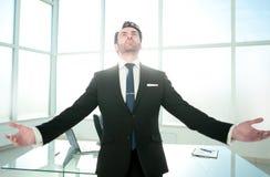 Sonhando a posição do homem de negócios em seu escritório fotografia de stock