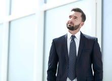 Sonhando a posição do homem de negócios em um escritório brilhante fotos de stock
