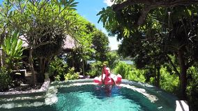 Sonhar a jovem mulher no roupa de banho encontra-se no colchão inflável do flamingo na piscina Muitas plantas verdes ao redor, oc vídeos de arquivo