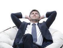 Sonhar o homem de negócios é descansar, sentando-se em uma grande cadeira macia fotografia de stock royalty free