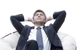Sonhar o homem de negócios é descansar, sentando-se em uma grande cadeira macia foto de stock
