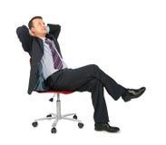 Sonhar o homem de negócios senta-se na cadeira do escritório Fotos de Stock Royalty Free