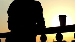 Sonhar o homem está com uma xícara de café em uma ponte do rio no por do sol video estoque