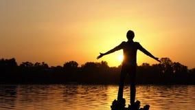 Sonhar o homem mantém as mãos de lado em um banco do lago no por do sol vídeos de arquivo