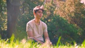 Sonhar o menino asiático está pendurando para fora apenas no parque, sentando-se na grama nos sunlights, atmosfera fresca da mola video estoque
