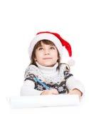 Sonho da menina sobre presentes e pensamento de que escrever em uma letra a Santa no branco fotos de stock royalty free