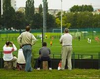 Sonho/pais dourados que prestam atenção ao jogo de futebol Foto de Stock