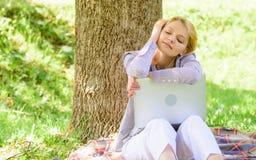 Sonho sobre o trabalho ou o internamento novo O portátil da menina que sonha no parque senta-se na grama Sonho sobre o projeto be imagem de stock