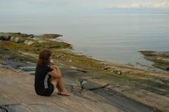 Sonhos da mulher do assento na pedra Fotografia de Stock