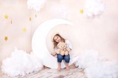 Sonhos doces Pouco menina bonito que senta-se na lua com nuvens e estrelas com um urso de peluche em no suas m?os e jogo Pouco as foto de stock royalty free