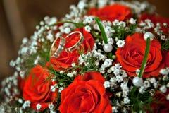 Sonne des jeunes mariés au bouquet de mariage des roses rouges Image libre de droits