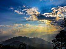 Sonnen-Strahlen von den Wolken über Bergen Stockfotografie