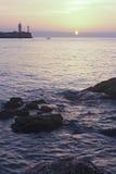 Sonnenaufgang über dem Meer mit dem Leuchtturm im Hintergrund Stockfotografie