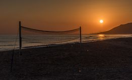 Sonnenaufgang über dem Meer mit Volleyballnetz lizenzfreie stockfotos