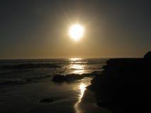 Sonnenaufgang über dem Ozean mit einem Boot im Wasser Stockfoto