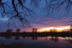 Sonnenaufgang über dem See mit Reflexion von bloßen Bäumen im Wasser Lizenzfreie Stockfotos