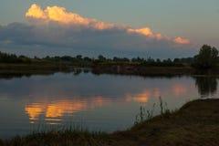Sonnenaufgang über dem See mit Reflexion von bloßen Bäumen im Wasser Stockfoto