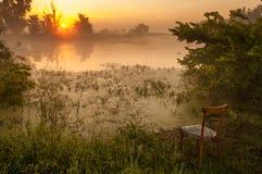 Sonnenaufgang über dem See mit Reflexion von bloßen Bäumen im Wasser Stockfotos