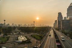 Sonnenaufgang über den Bangkok-Stadt-Skylinen Hochhäuser hinter einem Park mit Landstraße auf Vordergrund Stockfotos