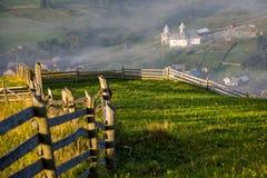 Sonnenaufgang über den grünen und nebelhaften Dörfern von Rumänien Lizenzfreie Stockbilder