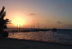 Sonnenaufgang über Dock Caye-Kalfaterer Stockfotos