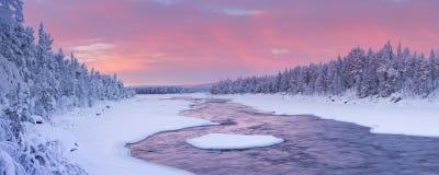 Sonnenaufgang über einem Fluss in einer Winterlandschaft, finnisches Lappland Lizenzfreie Stockfotos