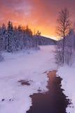 Sonnenaufgang über einem Fluss im Winter nahe Levi, finnisches Lappland Stockbilder