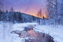 Sonnenaufgang über einem Fluss im Winter nahe Levi, finnisches Lappland Stockfotos