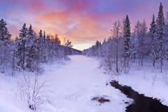 Sonnenaufgang über einem Fluss im Winter nahe Levi, finnisches Lappland Lizenzfreies Stockfoto