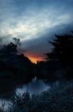 Sonnenaufgang über Fluss, orange Sonne im dunkelblauen Ton Stockfotografie