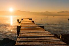 Sonnenaufgang über gefrorenem hölzernem Pier, Leman Lake und ikonenhaftem Snowy Mont- lizenzfreie stockbilder