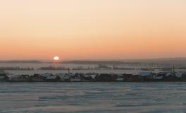 Sonnenaufgang über gefrorener schneebedeckter russischer rustikaler Landschaft Lizenzfreie Stockbilder