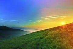 Sonnenaufgang über Hügeln in den Bergen mit grünes Gras und blauer Himmel wi Lizenzfreie Stockbilder