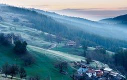 Sonnenaufgang über kleinem Dorf im Berg Stockfotografie