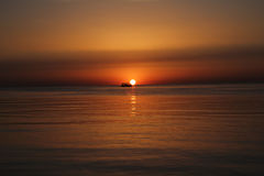 Sonnenaufgang über Meer mit Boot Stockfotografie