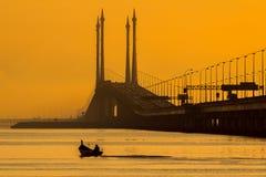 Sonnenaufgang über Meer und Brücke in Georgetown, Penang, Malaysia Stockfotos