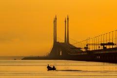Sonnenaufgang über Meer und Brücke in Georgetown, Penang, Malaysia Stockfotografie