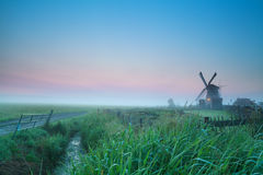 Sonnenaufgang über niederländischem Ackerland mit Windmühle Lizenzfreie Stockfotos