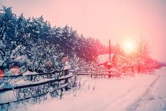 Sonnenaufgang über schneebedecktem Dorf Lizenzfreie Stockbilder