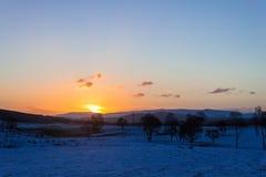 Sonnenaufgang über schneebedeckten Feldern Stockbilder